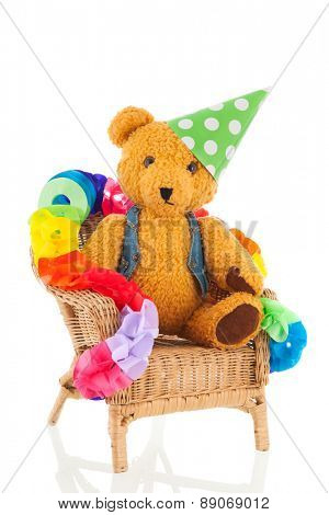 Funny stuffed bear in birthday chair isolated over white background