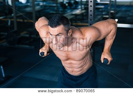 Handsome muscular man workout on bars in gym