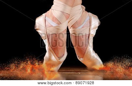 dancer in ballet shoes dancing in Pointe on a wooden floor