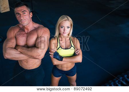 Group of a muscular man and fitness woman standing with arms folded in gym. Looking at camera