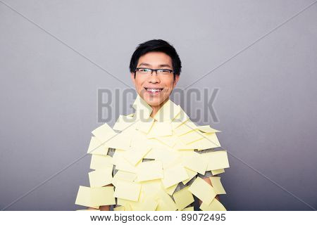 Cheerful asian man in glasses pasted stickers over gray background. Looking at camera