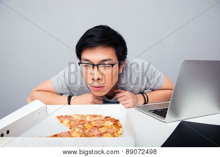 Young asian man sitting at the table and smelling pizza