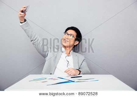 Happy businessman sitting at the table and making selfie photo on smartphone over gray background
