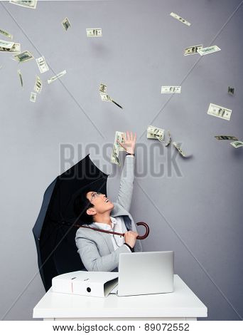 Happy asian businessman sitting at the table with umbrella with rain of money over gray background. Looking up