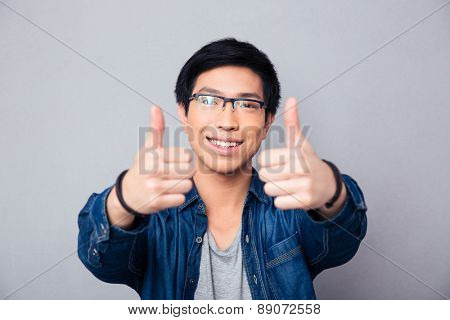 Portrait of a happy asian man with thumb up over gray background. Looking at camera
