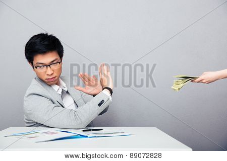 Asian young businessman gesturing stop sign while someone proposing money to him over gray background