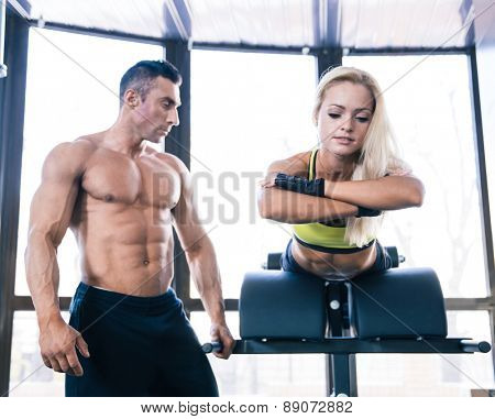 Spoty woman flexing back muscles on bench with muscular coach in gym
