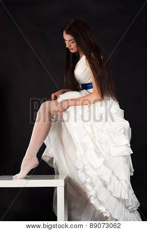beautiful woman in a wedding dress straightens stockings