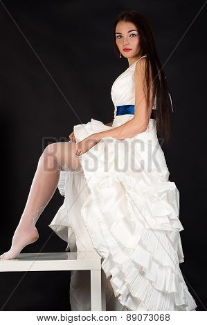 beautiful bride in a wedding dress straightens stockings