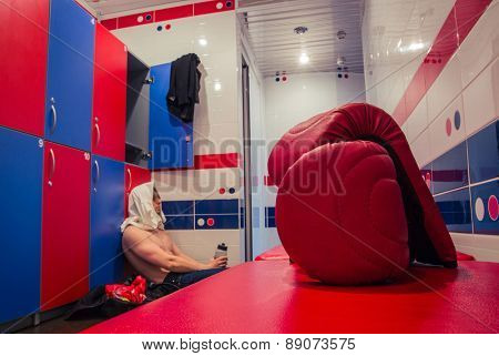 Tired man sitting on the floor in the locker room after finishing training