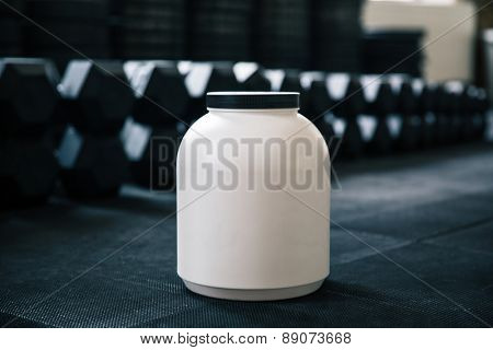 Closeup image of a plastic container with sports nutrition in gym