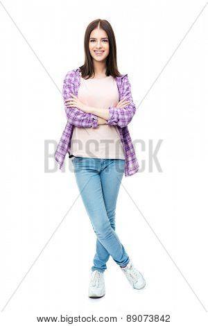 Full length portrait of a smiling cute female student standing over white background with arms folded and looking at camera