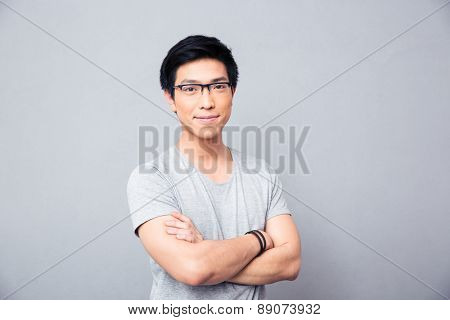 Portrait of a smiling asian man in glasses standing with hands crossed over gray background. Looking at camera