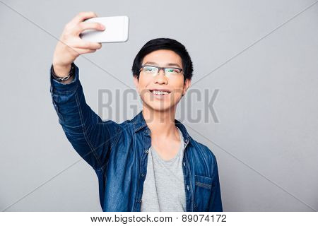 Happy young asian man making selfie photo on smartphone over gray background