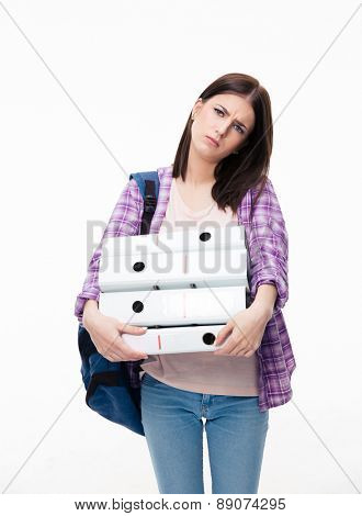 Portrait of unhappy young woman with backpack and folders stnading over white background and looking at camera