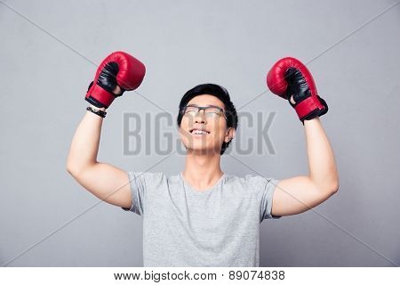 Asian man in boxing gloves rejoices victory over gray background