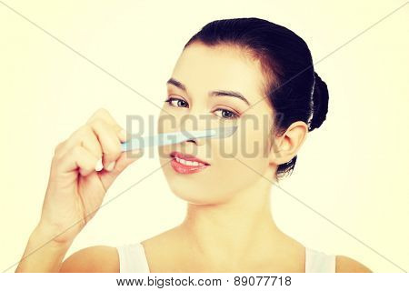 Scalpel near beautiful woman's face