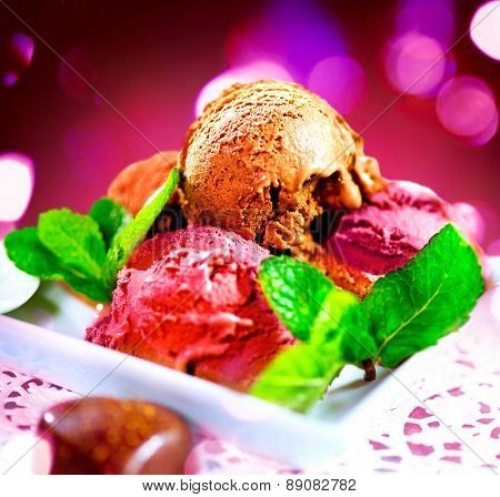Ice cream scoops with various flavours- chocolate,fruits and berry. Brown, red and pink icecream served with dark chocolate topping and mint