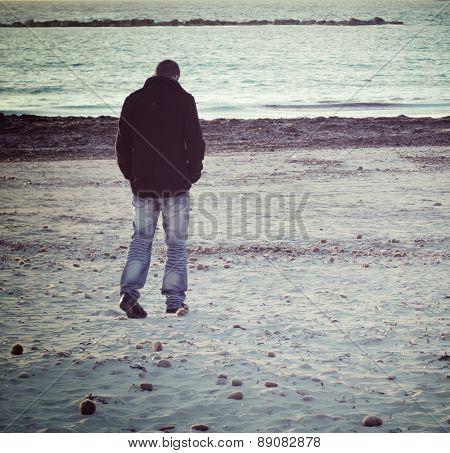 Man Walking By The Sea In Winter