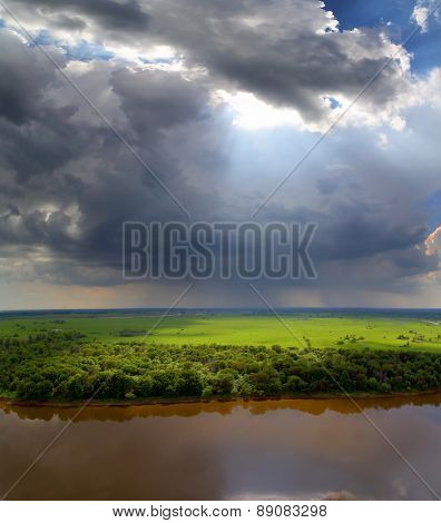 landscape with storm clouds, river and rain on horizon - view from height