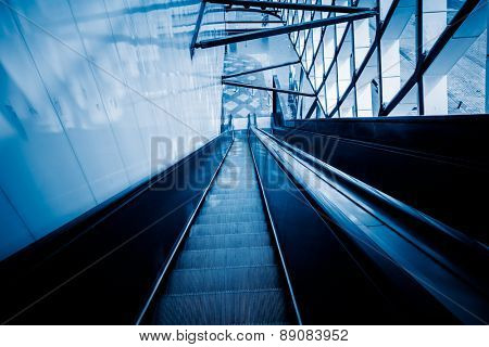 escalator of modern office building, blue toned images.