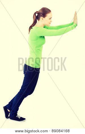 Beautiful woman trying to push the wall