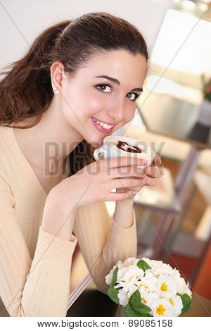 smiling girl in coffee drinking a cup of cappuccino
