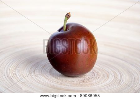 Plum on wooden plate - close up