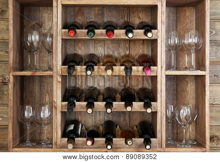 Shelving with wine bottles and glasses on wooden wall background