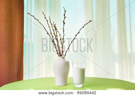 Willow twigs and glass of milk on table on curtains background