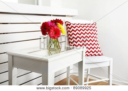 Modern interior with white chair and pillow near coffee table with colorful gerbera