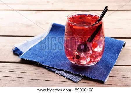 Glass of compote with red currant on wooden table with jeans cloth, closeup
