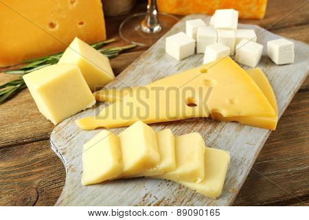 Various types of cheese on cutting board close up