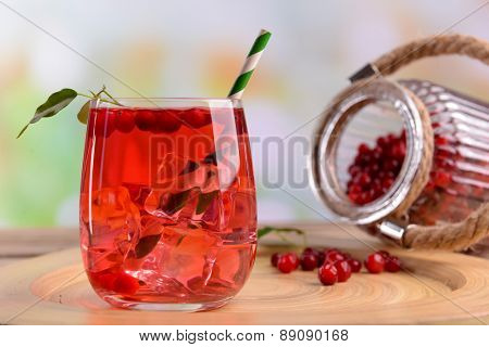 Compote with red currant in glass on wooden tray on light blurred background