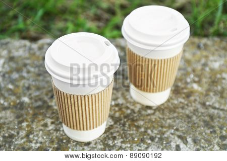 Paper cups on gray stone, outdoors