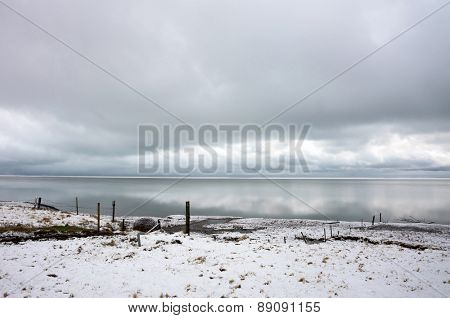View of snow covered plains, beaches and the sea in southern Iceland during winter.