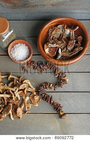 Dried mushrooms with spice on wooden background