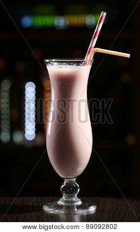 Glass of cocktail in bar on dark background