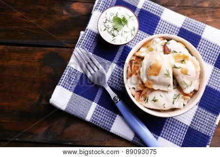 Tasty dumplings with fried onion in brown bowl, on wooden background