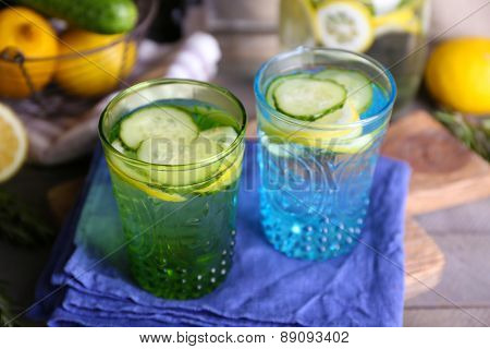 Fresh water with lemon and cucumber in glassware with napkin on wooden table, closeup