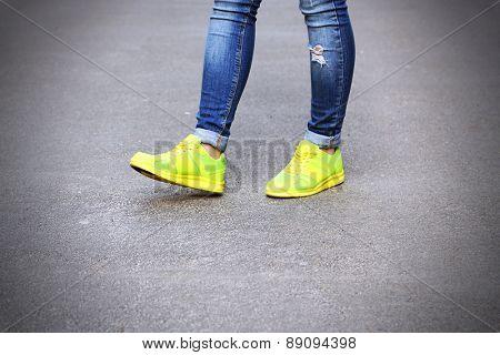 Female feet over gray asphalt background
