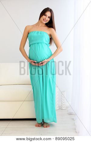 Pregnant woman standing near sofa in room