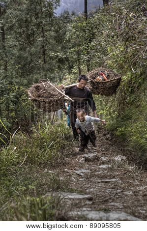 Father and son farmers returning from field work, rural China.