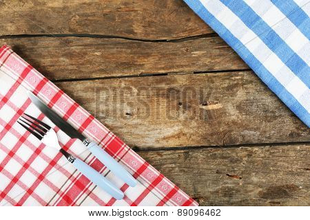 Checkered napkin with fork and knife on wooden table background