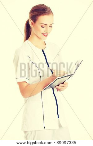 Female doctor in uniform writing results after research