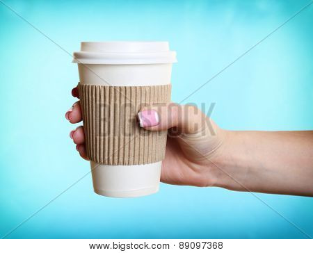 Female hand with paper cup on blue background