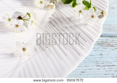 Acupuncture needles and flowering branch on plate on wooden table, closeup