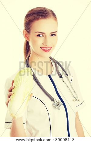 Female doctor in uniform holding cabbage