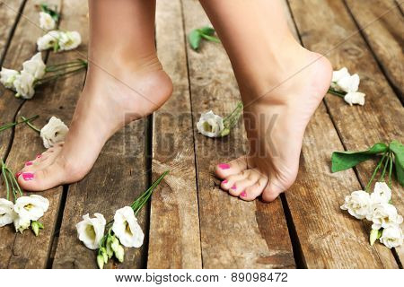 Beautiful female legs on rustic wooden floor background