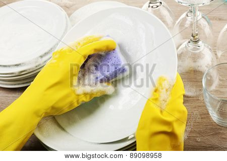 Female hand washing dish close up